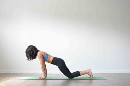 Woman doing chaturanga dandasana with knees on the floor