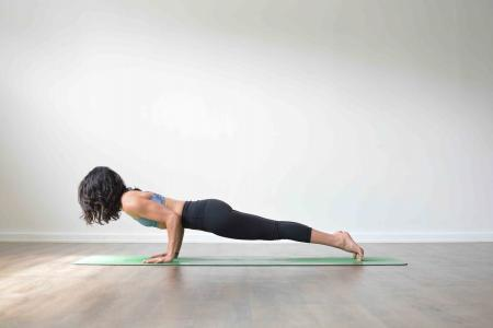 Woman doing Chaturanga dandasana Uppsala Yoga